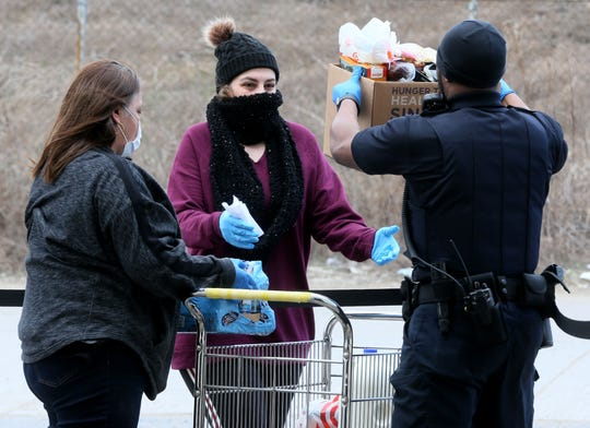 Yolanda Balderas, left, and security officer Charles Webb, right, give food to a patron at the United Migrant Opportunity Services (UMOS) Food Pantry. Food banks and pantries are facing high demand from Milwaukee residents as the food supply tightens during the coronavirus pandemic.