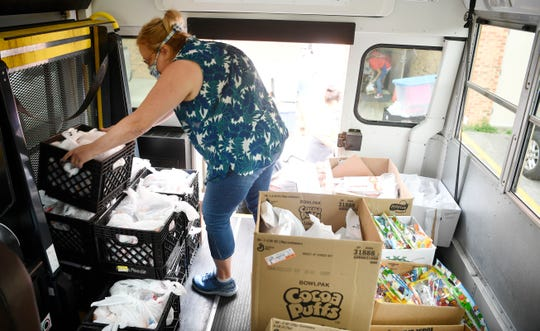Robbin Cross places meals inside a school bus that will make rounds in the Franklin Special School District and distribute meals to school children in Franklin, Tenn. Wednesday, April 8, 2020.