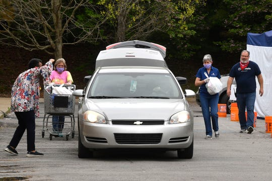 Cars line up to receive food distributions at Graceworks in Franklin, Tenn. Wednesday, April 8, 2020.