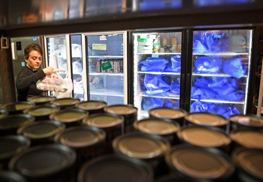 Jill Chasse picks out refrigerated and frozen food to be included in distributions at Graceworks in Franklin, Tenn. Wednesday, April 8, 2020.