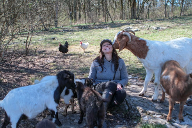 Atom the goat gives Amanda Baron a kiss. He is one of 14 pygmy goats on her family's mini farm.