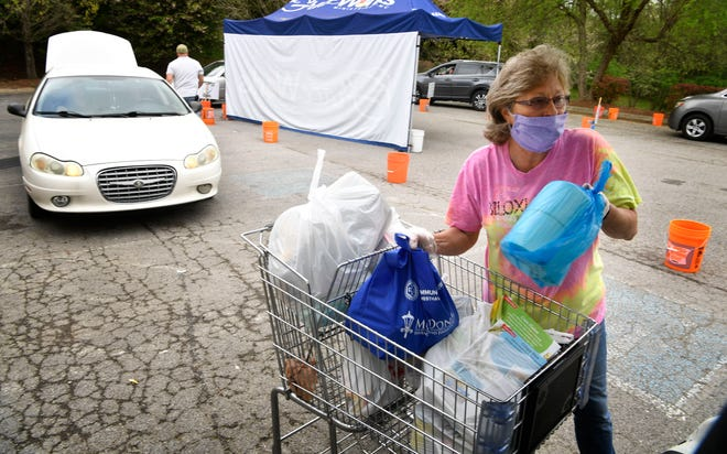 Nellie King loads a car that came to receive a food distribution at GraceWorks in Franklin on April 8, 2020.