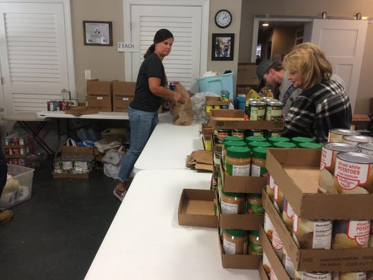 Staff and volunteers at The Ark, serving southern Cheatham County, keep a distance as they prepare food for clients.
