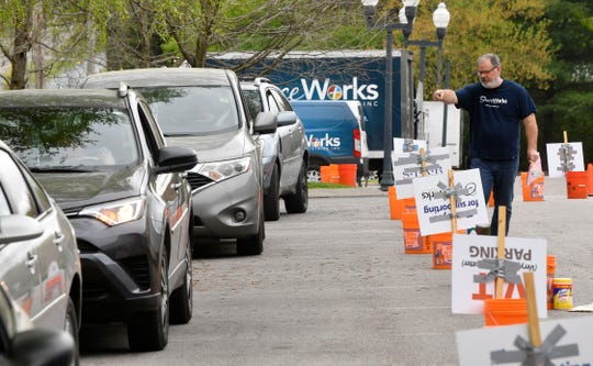 Greg Perry helps with the flow of cars lined up to receive food distributions at Graceworks in Franklin, Tenn. Wednesday, April 8, 2020.