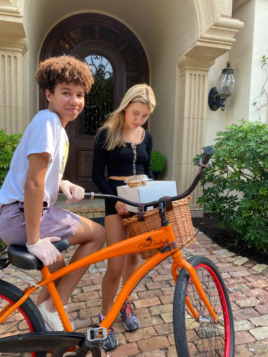 Ethan Brendel (left) and Emry Brandt-Zorbalas are on their way to deliver free baked goods to Naples police officers April 9, 2020. Hotel Escalante has opened a new bakery in its kitchen, in partnership with Yannick and Ana Brendel to serve the community and keep its employees working.