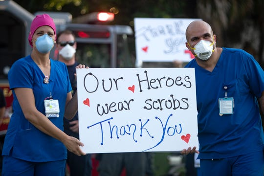 Registered Nurse Kristen Rizzo, left, and nursing director Jose Martinez, hold up a sign, made by local first responders for the staff at NCH North Naples Hospital on Wednesday, April 8, 2020.