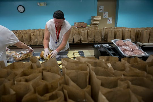 Michael Yantis and a volunteer prepare 300 sandwiches to be handed out at dinner at the Salvation Army Wednesday evening. The Salvation Army has been serving many more families and individuals since the pandemic hit and the Governor issued stay at home orders forcing many people out of jobs.