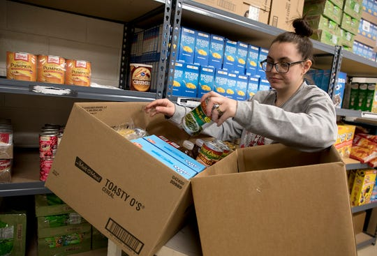Paige Gantt goes through the Salvation Army's food pantry selecting items she needs. The Salvation Army has been feeding more people than usual due to the loss of jobs from the pandemic.