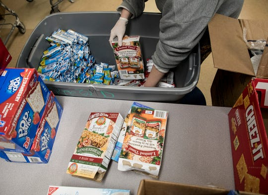 A volunteer organizes food at the Salvation Army.