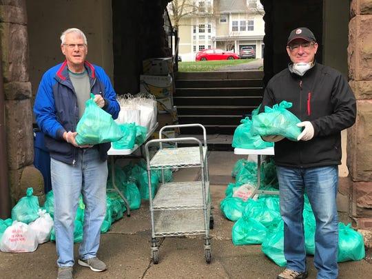 Volunteers help distribute meals from Toni's Kitchen.
