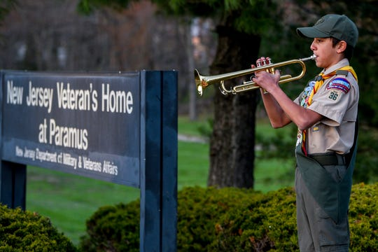 Alex Saldana, 13, a Boy Scout in Oradell Troop 36 and a Life Scout, plays the Marine Corps Hymn and Taps in front of the New Jersey Veterans Home in Paramus on Thursday April 09, 2020. Saldana plays to honor the 37 military veterans who have died at the the New Jersey Veteran's Home in the past two weeks. At least 10 veterans died from the coronavirus.