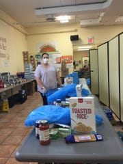 Social worker Jennie Vega prepares bags of food.