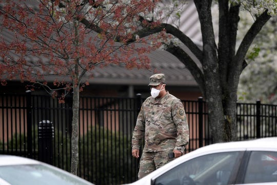 A member of the U.S. National Guard walks into the New Jersey Veteran's Home in Paramus on Thursday, April 9, 2020.