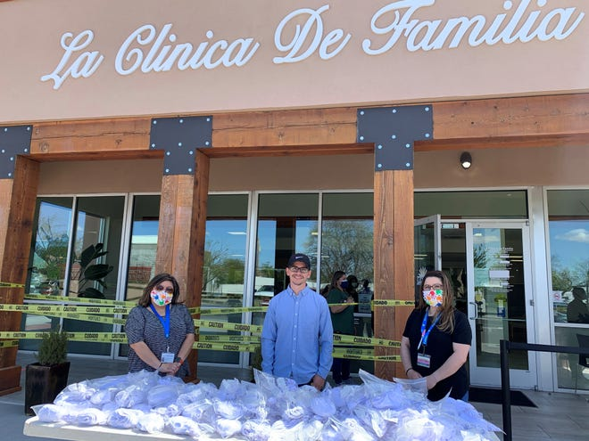 Johnny Pacheco, owner of SouthWest Sublimation, stands with La Clinica de Familia healthcare workers in front of 1,000 face masks donated by the community and made by SouthWest Sublimation Thursday, April 9, 2020.