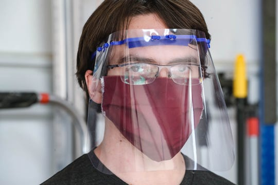 Michael Harris models a face mask shield, one of the 3D printed components he makes in his garage in Las Cruces on Thursday, April 9, 2020.