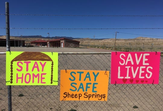 Community members in Sheep Springs are reminded about staying at home to combat the new coronavirus. The signs are pictured on April 5 at the flea market in Sheep Springs.