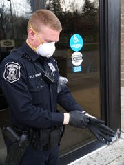 Farmington Hills Police Officer Pat Moran puts on some protective gear on April 9, 2020. During the time of the coronavirus pandemic officers are donning protective gear whenever interacting with the public.