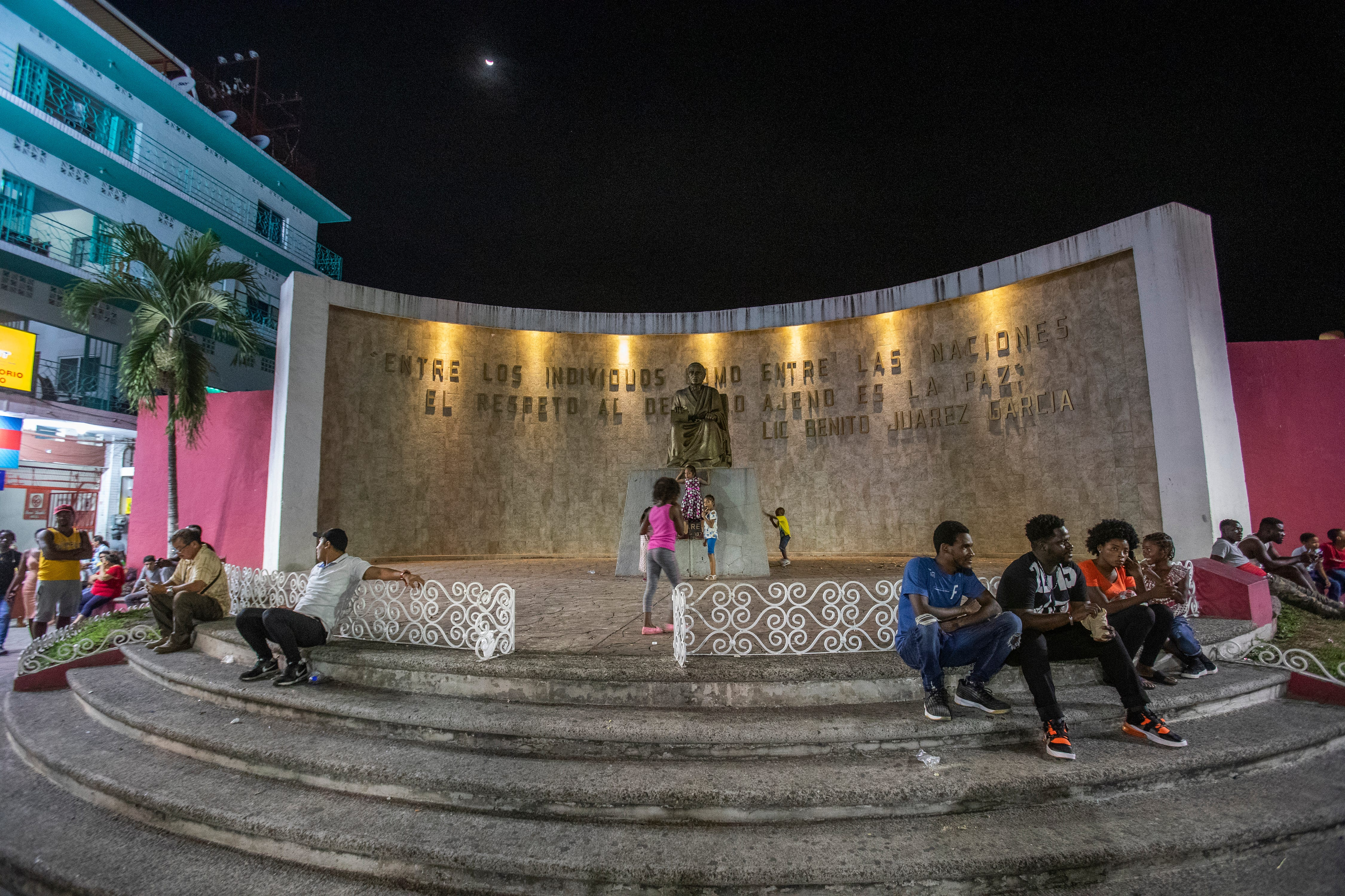 A plaza dedicated to Mexico's ethnic groups has become a meeting place for migrants from all over the world in Tapachula, Chiapas. In the background, the statue of Mexico's first indigenous, and most celebrated, president is seen in background.