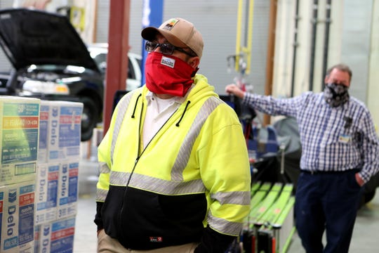 City of Indio Traffic Signal Technician Richard Mercado, left and Fleet Services Operations Manager Dennis Wolbert wear masks as they talk inside the city yard facility in Indio, Calif., on Wednesday, April 8, 2020.