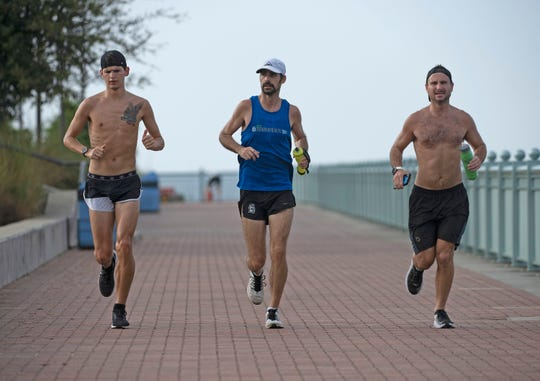 UWF cross country coach, Caleb Carmichael, center, is joined by Justin Watson and Josh Clark as he runs his fourth marathon in as many days on Thursday, April 9, 2020. Carmichael is running seven marathons in 7 days to raise money for Argo Pantry and Feeding the Gulf Coast as a way to help out during the COVID-19 pandemic.