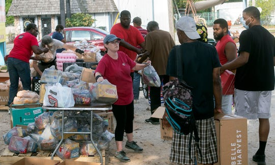 Dozens of people gather outside the Epps Christian Center for a food giveaway on April 9.