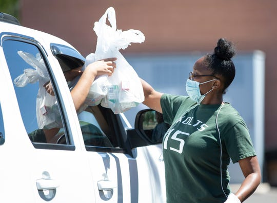 Zacona Michaux hands out lunches at Edison Elementary School on April 9, 2020. Mesa Public Schools has scaled back meal distribution and since closed the Edison site. Meals can be picked up at Kino Junior High on Mondays, Wednesdays and Fridays instead.