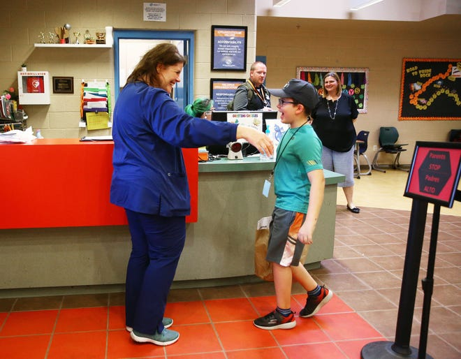 Apr. 8, 2020; Phoenix, AZ, USA; Robyn Hale, a nursing director at Banner Health picks up her 7-year-old son Andrew from the Boys and Girls Club Robson Branch in north Phoenix. Mandatory Credit: Rob Schumacher/The Arizona Republic via USA TODAY NETWORK