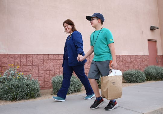 Robyn Hale, a nursing director at Banner Health picks up her 7-year-old son Andrew from the Boys and Girls Club Robson Branch in north Phoenix.