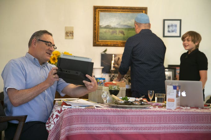 Rabbi Dean Shapiro (left) of Temple Emanuel in Tempe, angles his laptop towards his partner, Haim Ainsworth and their son, Jacob Shapiro-Ainsworth, 11, so others online can see them lighting candles as Rabbi Shapiro leads an online Seder during the first night of the Jewish holiday of Passover at their home in Tempe on April 8, 2020. The Seder which included members from Temple Emanuel was being held online because of the coronavirus pandemic.