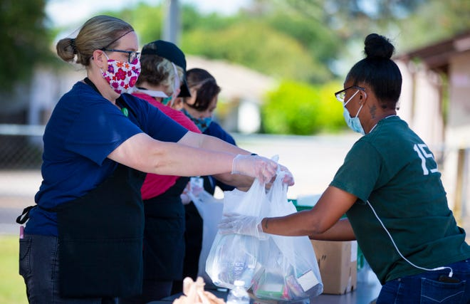Mindi Lamoreaux, left,  and Zacona Michaux hand out meals at Edison Elementary School in Mesa on April 9, 2020.
