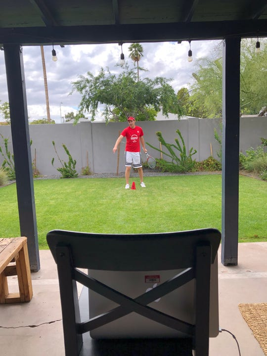 Brophy Prep boys tennis coach Eric Chalmers records video footage of himself