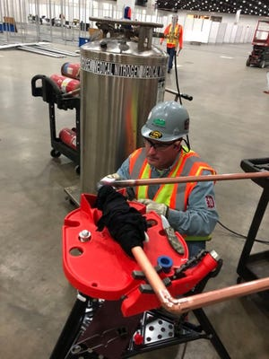 St. Clair resident and Detroit Plumbers Local 98 member Ryan Lyle does work on the oxygen system for the Detroit TCF Center, which was converted into a field hospital to take COVID-19 cases.