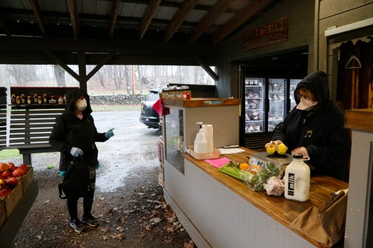 Jane Hollenberg of Red Hook keeps her distance while Crystal Carolan helps her at the Migliorelli farm stand in Rhinebeck on April 9, 2020.