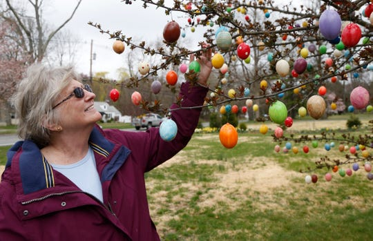 Louann Haussermann checks over some of the over 2,000 Easter eggs she used to decorate one of the trees at her home in the Town of Poughkeepsie on April 8, 2020.