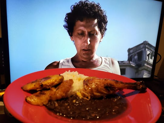 "Alexis Diaz de Villegas as Juan in ""Juan de los Muertos"" (Juan of the Dead) -- with roasted chicken and rice and beans. (Carolina A. Miranda/Los Angeles Times/TNS)"