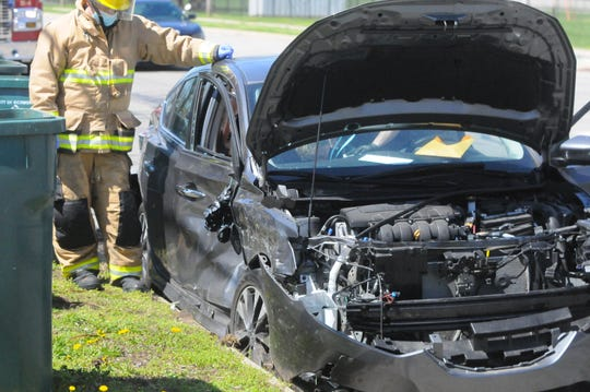 Officer Ami Miller investigates inside a Nissan Sentra that was involved in an accident Wednesday, April 9, 2020, at South L and South 13th streets.