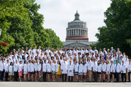 University of Rochester School of Medicine and Dentistry's first-year med students assemble for a photo on the quad steps after the white coat ceremony on Aug. 12, 2016, at the Interfaith Chapel August 12, 2016.  The school conferred degrees Tuesday on 99 members, accelerating graduation so they could begin practicing during the novel coronavirus pandemic.