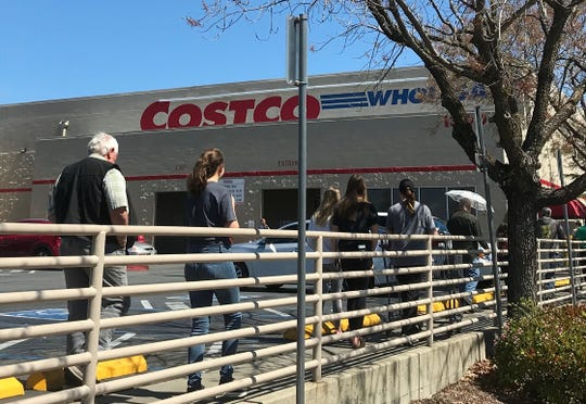 Customers line up to enter the Costco store in Redding where an employee was recently put under quarantine for coming in close contact with someone with the coronavirus.