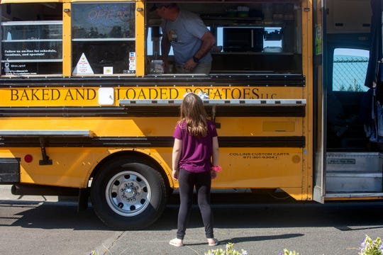Peyton Mitchell, 7, asks for a baked potato on April 8, 2020 at Stayton Elementary School. Every Wednesday and Friday at lunchtime, Baked and Loaded Potatoes food cart has been giving away cheesy baked potatoes to children.