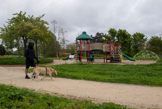 A person walks their dog in front of a playground covered in caution tape on April 8, 2020. Parks around Salinas have been closed due to the rise of COVID-19 cases in Monterey County.