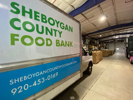 A Sheboygan County Food Bank truck sits parked in a warehouse.