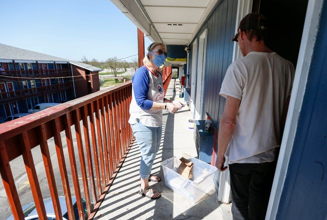 In this file photo from April, a volunteer delivers meals to a homeless man at the Fairvue Studios motel.