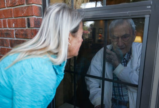 Debra Appleby visits with her 99-year-old father Jim Dowell through a window and on the phone at the Morningside of Chesterfield Village assisted living home on Thursday, April 9, 2020. Due to COVID-19 assisted living homes and nursing homes are not allowing visitors to reduce the potential exposure of residents.