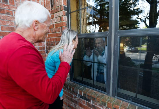 Debra Appleby and her husband John visit with her 99-year-old father Jim Dowell through a window and on the phone at the Morningside of Chesterfield Village assisted living home on Thursday, April 9, 2020. Due to COVID-19 assisted living homes and nursing homes are not allowing visitors to reduce the potential exposure of residents.