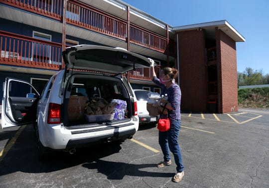 Peggy Francka, a volunteer from Gathering Friends, grabs meals from the back on a SUV to distribute to homeless at the Fairvue Studios motel on Wednesday, April 8, 2020. Grants from Mercy and Community Foundation of the Ozarks made it possible to house about 80 homeless people in hotels during the COVID-19 pandemic.