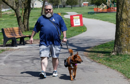 Michael Gordy walks with his service dog Roxie at Owen Park in Republic on April 8.