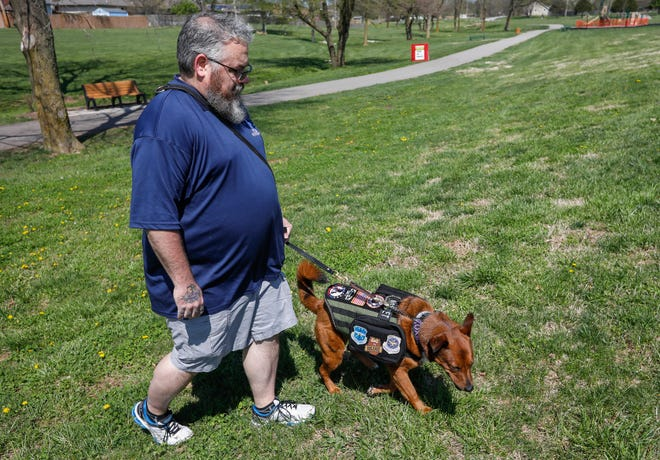 Michael Gordy, a Coast Guard and Air Force veteran who struggles with post-traumatic stress disorder, walks with his service dog Roxie at Owen Park in Republic on April 8.