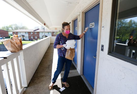 Peggy Francka, a volunteer from Gathering Friends, knocks on a door at the Motel 6 on north Glenstone Avenue to deliver food to a homeless person on Wednesday, April 8, 2020. Grants from Mercy and Community Foundation of the Ozarks made it possible to house about 80 homeless people in hotels during the COVID-19 pandemic.