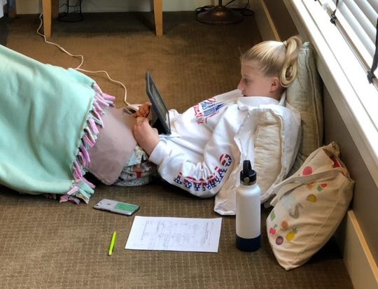 Ella Collier, a seventh-grader at South Junior High in St. Cloud, gets comfortable while distance learning at her home in St. Augusta.