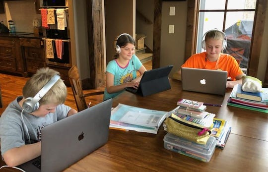 Ethan, Ave and Ella Collier complete schoolwork via distance learning at their home in St. Augusta.
